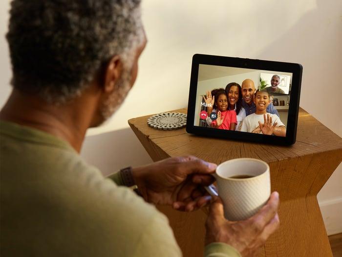 Man talking to family through an Echo Show device.