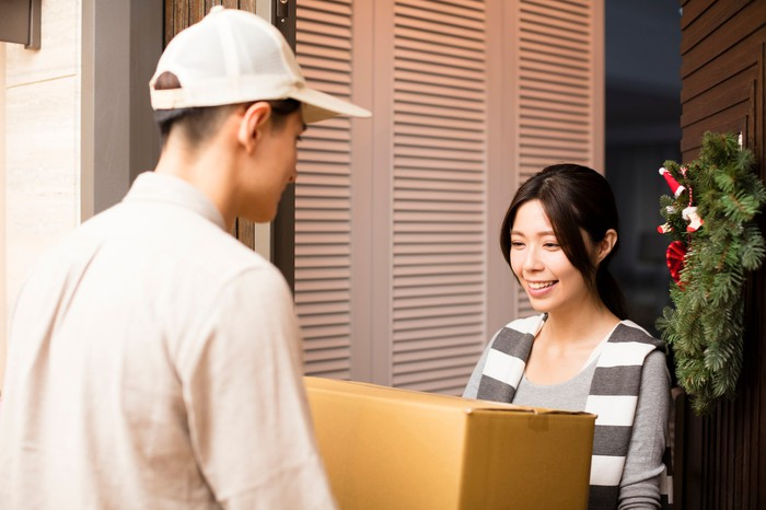 Young woman receiving package from delivery man
