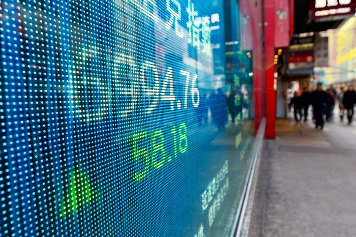 Electronic board displaying stock prices along a street.