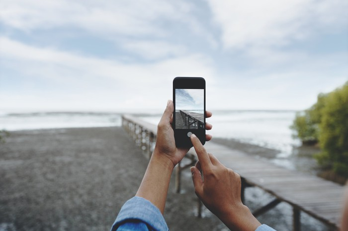 A person taking a photo of the a dock and shore.