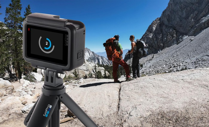A GoPro Hero 7 Black pointed at two hikers.