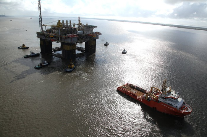 Oil rig at sea with several vessels surrounding it.