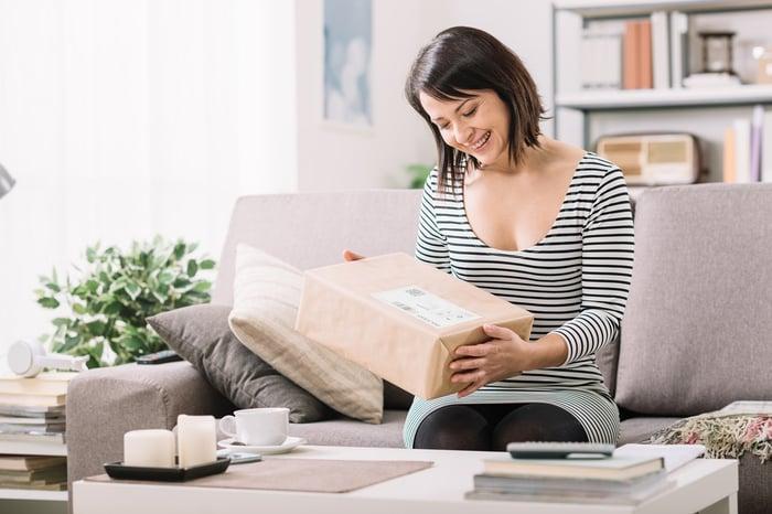 Smiling woman opens e-commerce shipment.