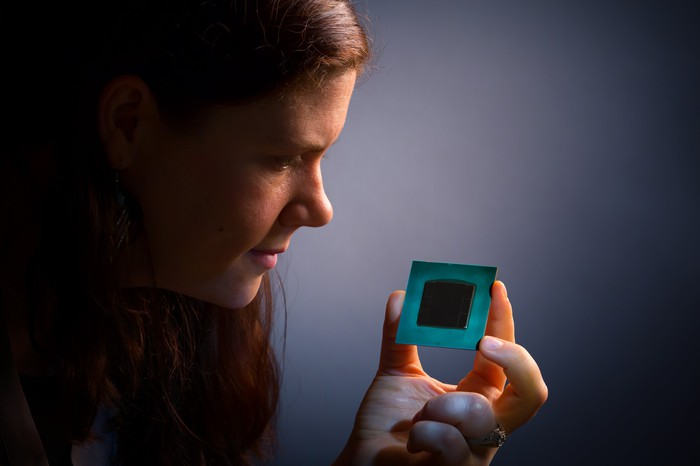 Woman holding a computer chip.