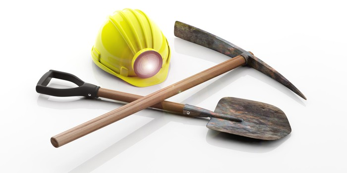 A pick, shovel, and miner's hat on a white background.