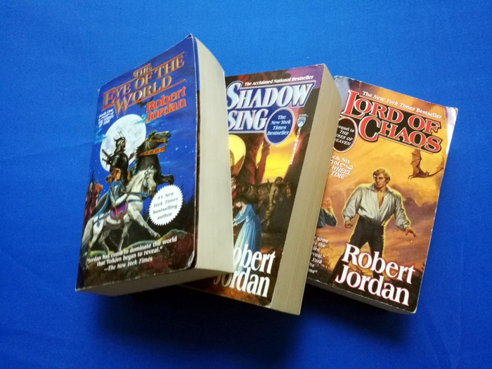 Three of the books from Robert Jordan's Wheel of Time series, arranged on a blue backdrop.