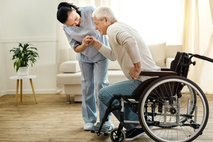 Woman in scrubs helping senior man out of wheelchair.