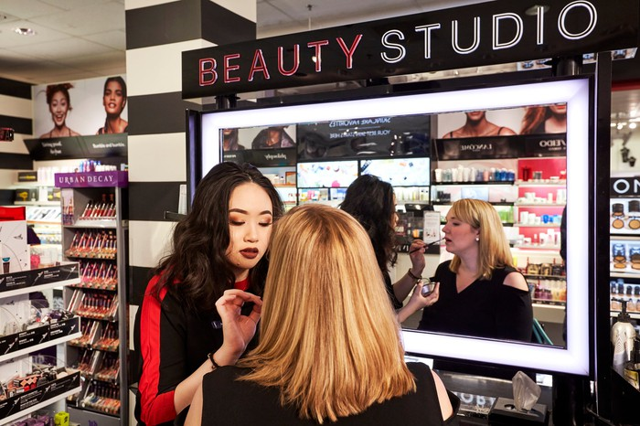 A woman having makeup applied by another woman at a Sephora salon inside a J.C. Penney.