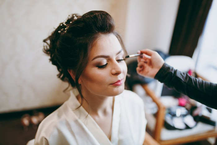 A bride having make-up applied.