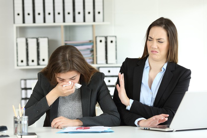 A woman looks on as another sneezes in the workplace