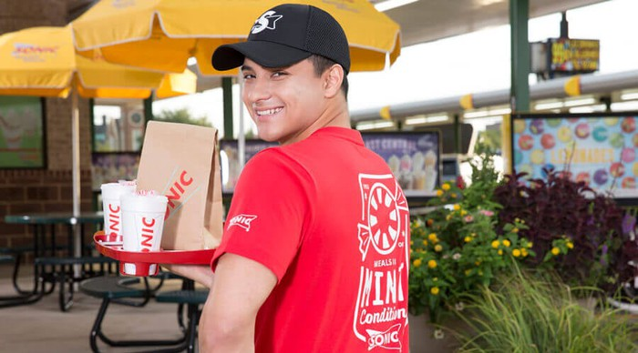 A Sonic carhop smiling while delivering a meal on a tray.