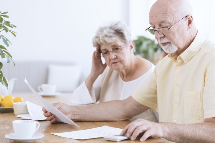Senior couple looking at documents while man uses calculator