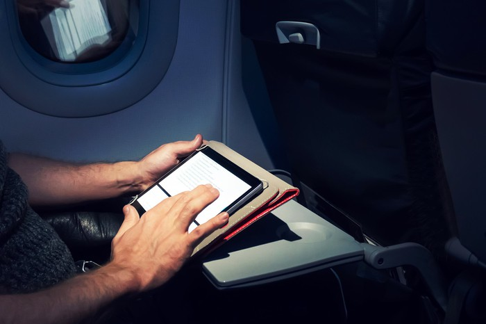 A man uses a tablet on a plane.