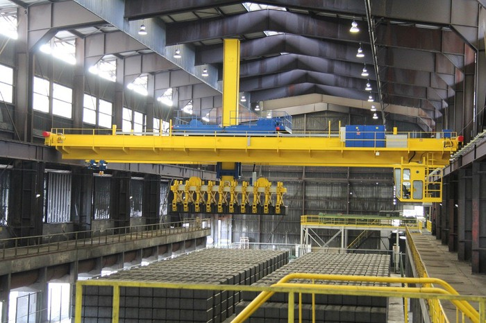 Manufacturing facility with high ceilings and yellow equipment over hundreds of large gray blocks.