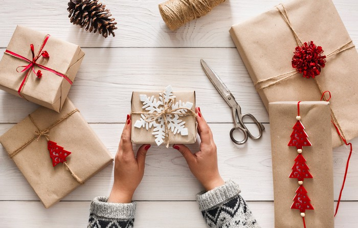 Woman holding a wrapped gift with other wrapped gifts and scissors spread out near her
