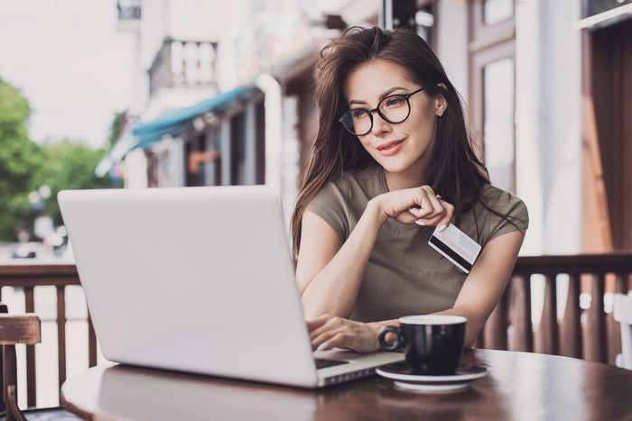 A bespectacled woman shopping online while on her laptop and holding a credit card.