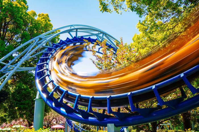 A yellow roller coaster speeds through a corkscrew loop
