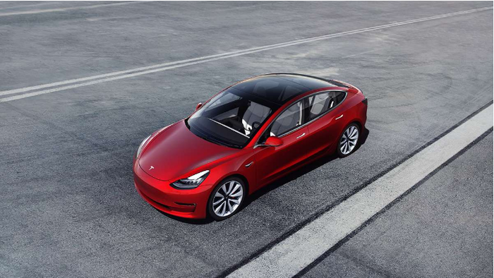 View from slightly above and to the side of a driverless red Model 3 on a highway.