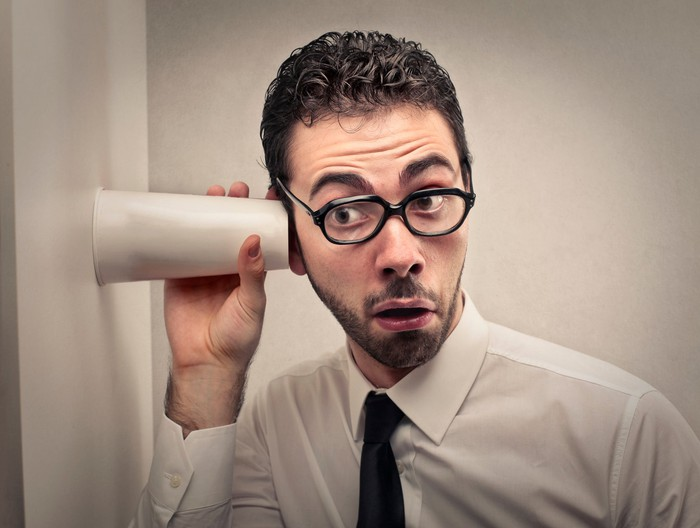 A man in glasses holds a cup to his ear and a wall attempting to listen to what's  on the other side.