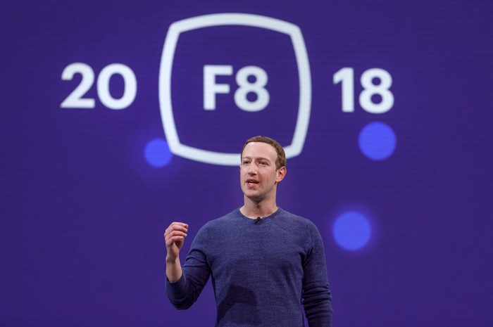 Facebook CEO Mark Zuckerberg speaking in front of a blue screen with 20, F8 (circled), and 18 on it.