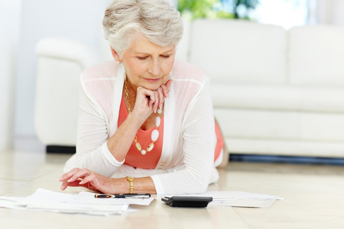 Senior woman looking at papers and calculator
