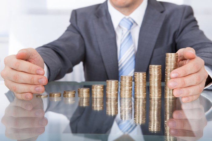 A man in a suit puts his hands around a series of increasingly taller stacks of coins.
