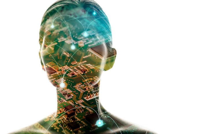 Silhouette of woman's head with computer motherboard overlaid on top.
