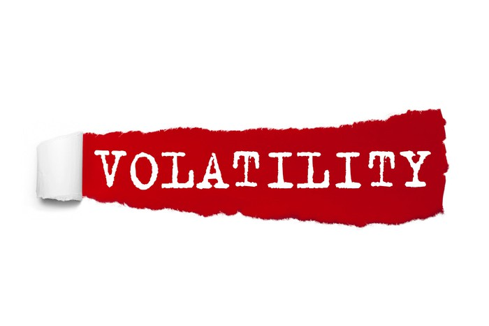 The word volatility written under the curled piece of red torn paper