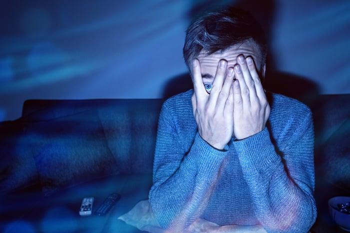 Man peeking between fingers to watch screen.