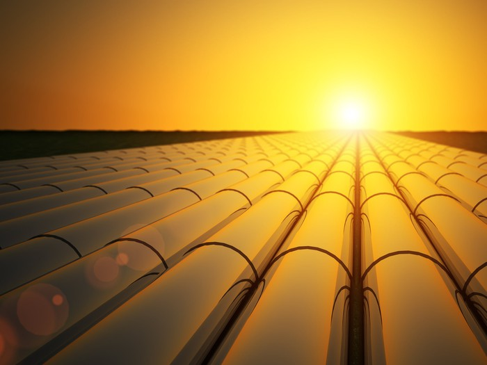 A field of oil pipes while the sun sets on the horizon.