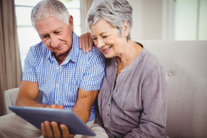 Senior couple looking at an electronic tablet.