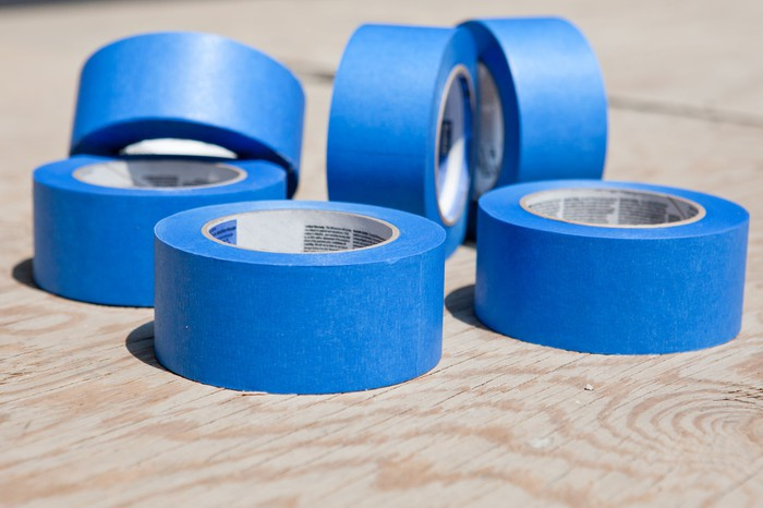Six rolls of blue tape on a wooden table.