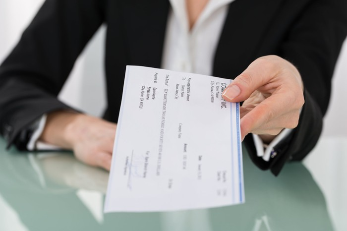 Woman in business suit holding out a paycheck.