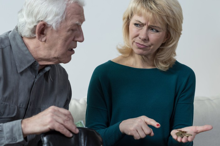 A confused elderly man looking at a small pile of coins in a woman's hand to his left.