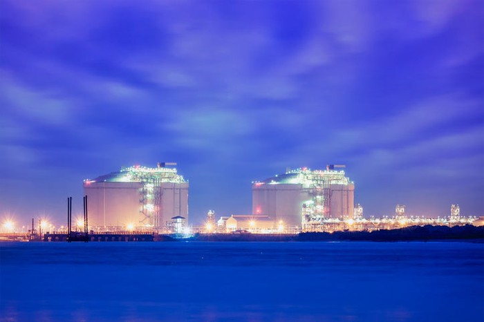 Large LNG storage tanks as viewed from just off shore.