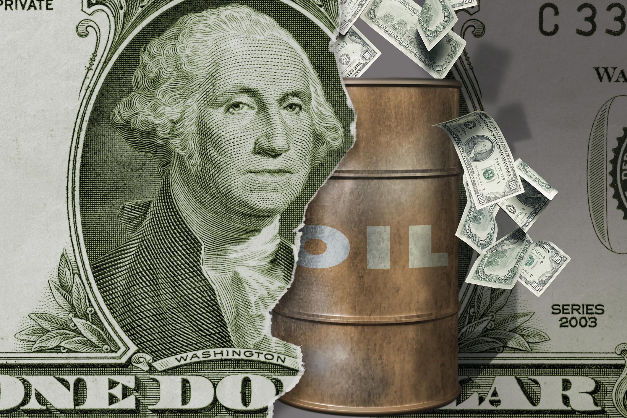 A barrel of oil coming through a dollar bill.