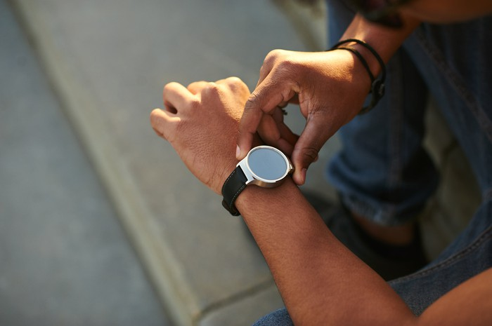 A man interacts with his fitness tracker.