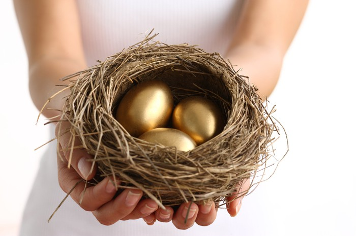 Hands holding nest with three golden eggs