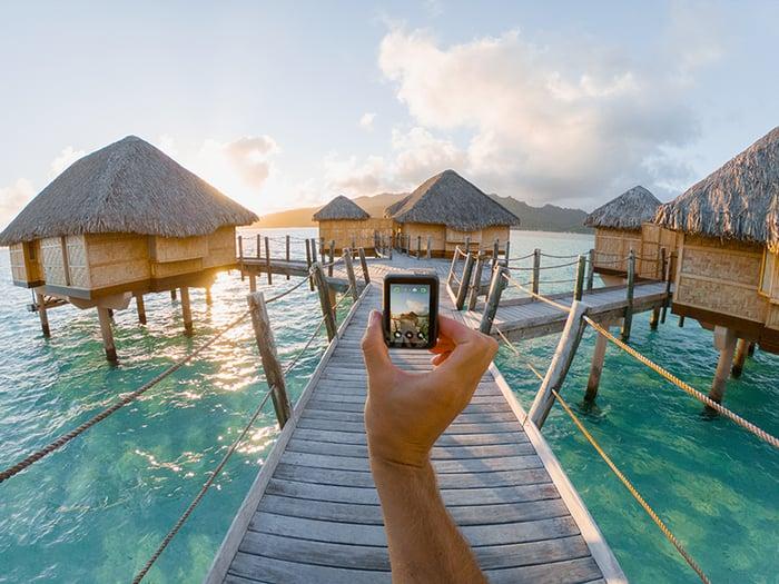 A GoPro Hero7 Black camera being held by hand walking through a Tahitian beach resort.
