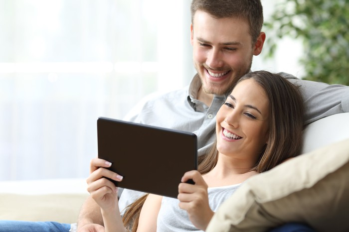 Couple sitting on a couch looking at a tablet and smiling.