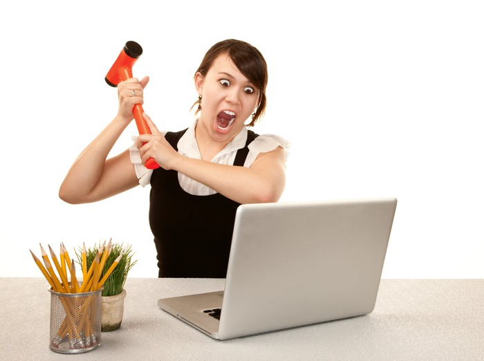Businesswoman screaming and swinging an orange mallet at her laptop.