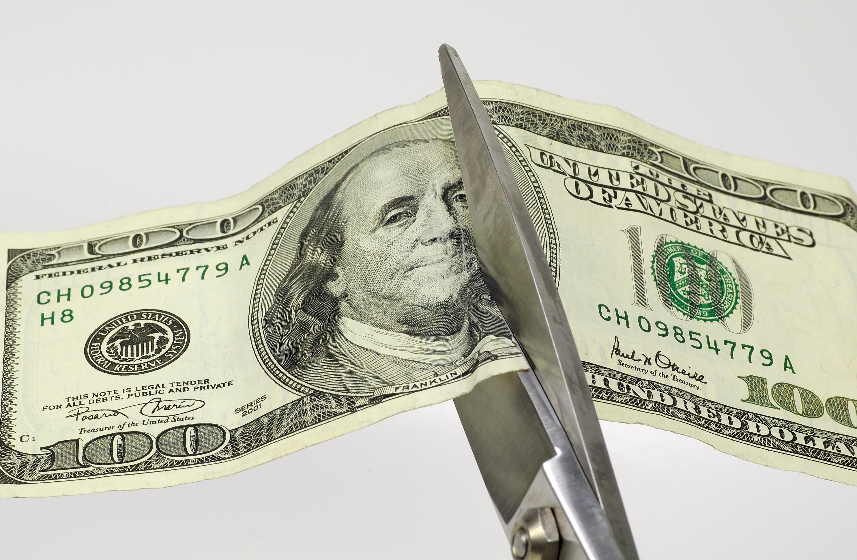 Scissors cutting through a $100 bill.