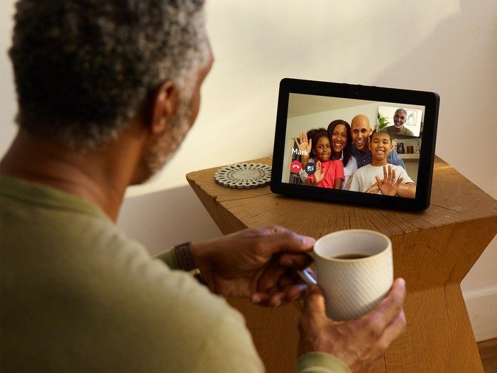 Man using an Echo Show device to talk to family members.
