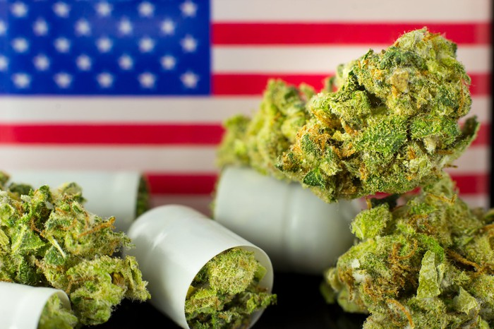 Marijuana buds spilling out of bottles in front of an American flag.