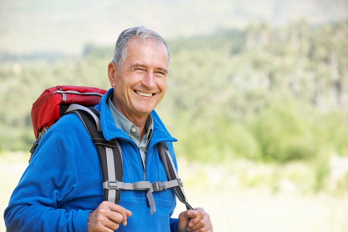 Smiling older man outdoors wearing a backpack