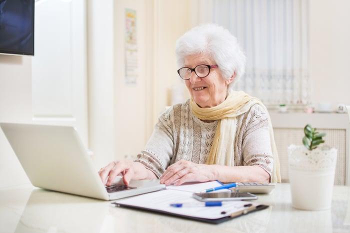Smiling senior woman typing on laptop