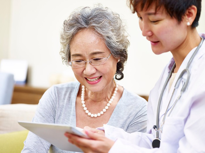 Asian patient and doctor looking at a chart.