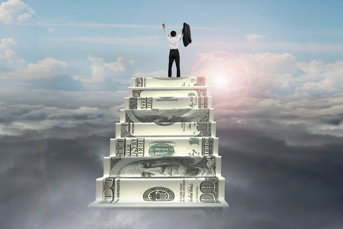 A man celebrating after climbing to the top of a staircase made out of money overlooking the clouds with a brightly shining sun.