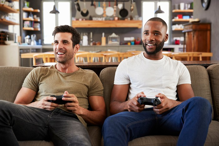 Two men sitting on a couch and playing a video game.