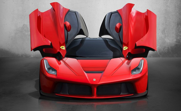 Red Ferrari car with its side-opening doors raised in the air.